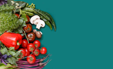 Top view with space for text. Vegetables arranged aside on green background diverse type of vegetables. Banco de Imagens