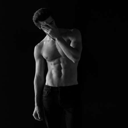 Photo black and white. Portrait of an athletic man with a shirtless tanned torso. Studio shoot. Foto de archivo
