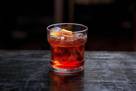 Closeup of a God father cocktail in short glass, gin, standing on the bar counter, isolated on a red light background. Stock Photo