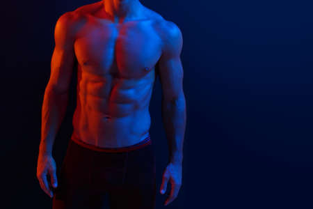 Cropped image of a strong athletic young man model showing six pack abs, over dark purple neon background.
