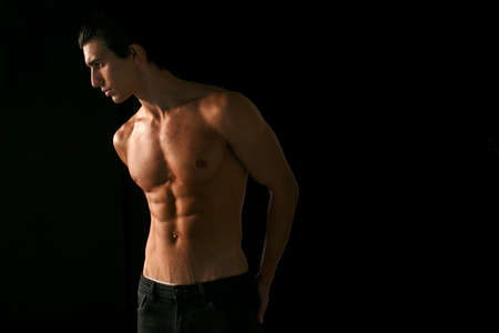 Profile portrait of a young man with shirtless torso with tanned skin, over black background. Space for text. Foto de archivo