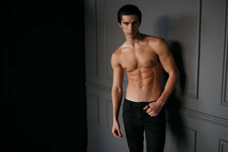 Portrait of a young man with shirtless torso with tanned skin, over black background. Space for text. Foto de archivo