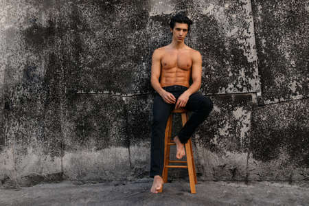 Full length portrait of attractive young man with naked torso near old black wall, seated on high chair. Space for text.