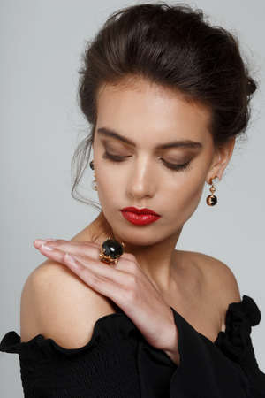 Portrait of a beautiful brunette woman with makeup, in black dress, showing luxury jewellery, over white background.