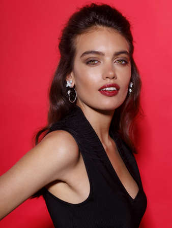 Closeup portrait of a beautiful young woman with makeup, wear in black dress, luxury jewellery, over red background Foto de archivo