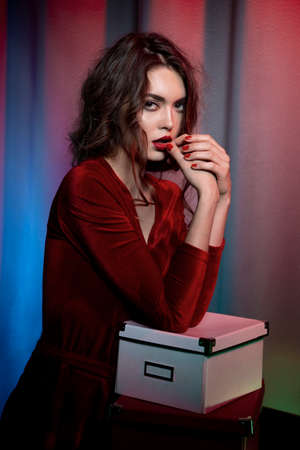 Sensual lady in red dress, looking elegant at the camera. Red lipstick and nail. Beauty content. Banque d'images
