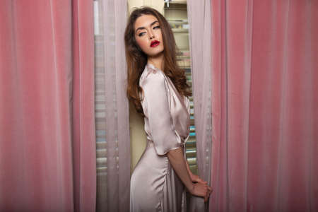 Fashion caucasian model with hairstyle and makeup, dressed in silk slim dress posing seductive near window in bedroom.