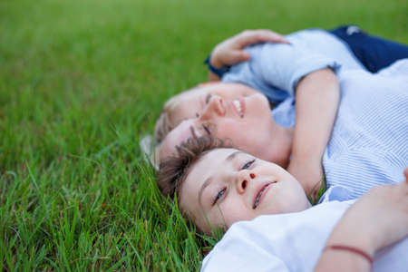 Close up portrait of a cheerful family lying on beautiful summer meadow enjoying and having fun. Copy space.