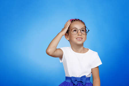 Frontal portrait of a confused pretty little girl in eyeglasses isolated blue background.