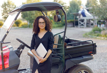 Woman with curly hair in black dress holding in hands a laptope, poses near vehicle and smiling. Small bussines content.