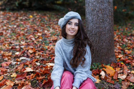 The young woman dressed in a beret and autumn clothes is sitting on the leaves near to a tree in the autumn season.