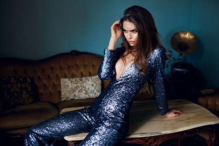 Sexy young woman in silver blue sequin chemise with decolletage. Fashion model with curly brunette hairstyle and makeup. Banque d'images