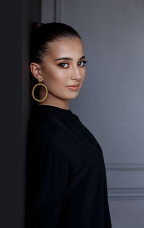 Profile portrait of attractive fashion girl in elegant black shirt and gold earrings, over grey background. Stock Photo