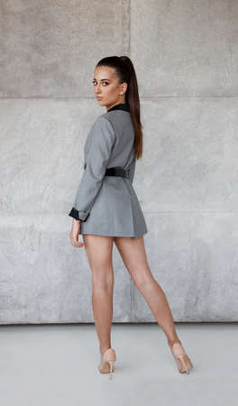 Back view of a confident girl in grey jacket and beige high heel, looking at camera, over concrete background.