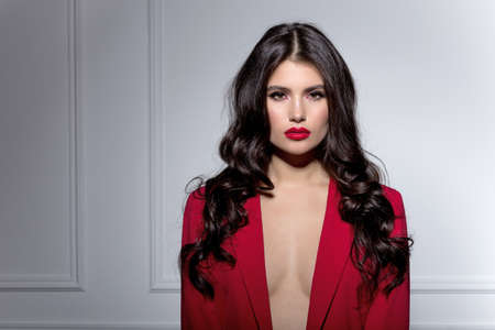Attractive brunette young woman face cosmetic makeup wear red suit, looking at camera, over white background.