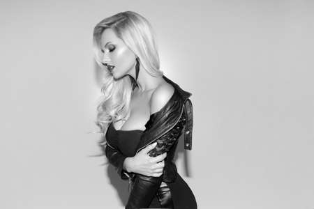 Young stylish blonde young woman in black leather jacket posing in studio. Black and white photo.