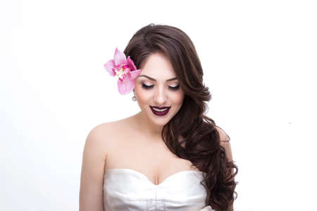 Frontal portrait of a young fashion model with closed eye and make up, white background, bride with flower in hair.