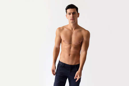 Sexy young man with nacked torso in black jeans, posing in studio, looking at camera, isolated on a white background. Stock Photo