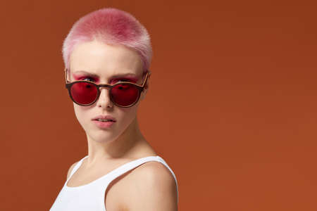 Nonconformist young woman magenta short hairs pink with red sunglasses, over brown background. Space for text.
