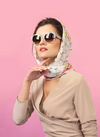 Front portrait of a stylish young woman wearing elegant clothins, retro in sunglasses, over pink background. Standard-Bild