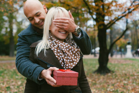 recieving: Man keeps his girlfriend eyes covered while she recieving a gift