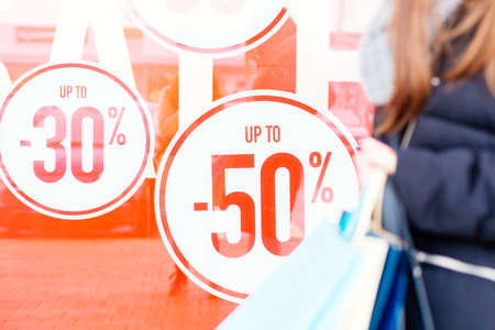 Woman holding shopping bags in front of store window with copy space. Focus on the store window. Sale Stock Photo