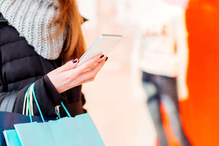 Closeup of woman using her smartphone and holding shopping bags Stock Photo
