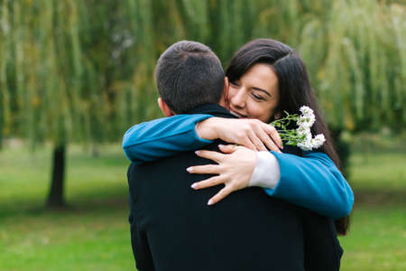 he laughs: Young couple hug each other in a park. The young girl laughs and wraps her arms tightly around her boyfriend as he playfully lifts her up and closer to him Stock Photo