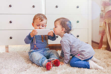 Two little kids sitting on the floor and playing with smartphone Stock Photo