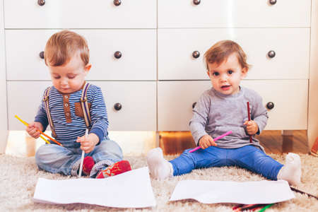 Happy little girl and boy sitting on the floor and painting Stock Photo
