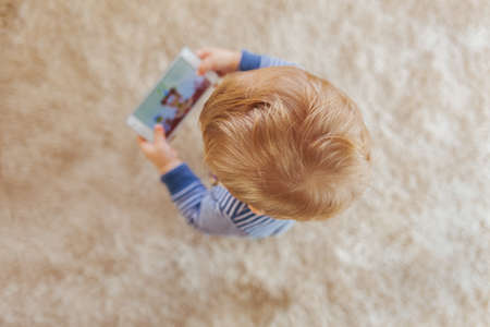 Little boy using smartphone, top view
