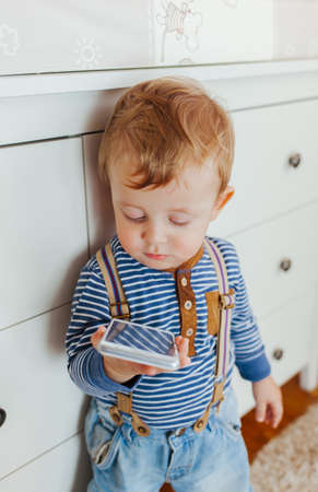 ittle: Cute ittle boy standing and using smartphone indoors Stock Photo
