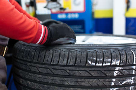 Mechanic removes car tire closeup. Machine for removing rubber from the wheel disc
