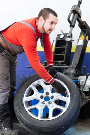 Mechanic removes car tire. Machine for removing rubber from the wheel disc Stock Photo