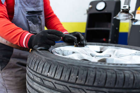 skill: Closeup of mechanician check car tire pressure and filling air in the tires in the auto service garage Stock Photo