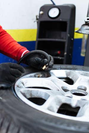dirty car: inflating the automobile wheels via a pump closeup