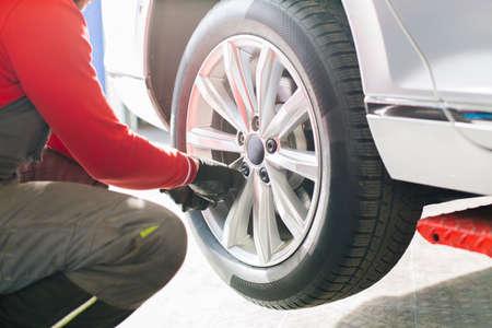 Mechanician changing car wheel in auto repair shop closeup