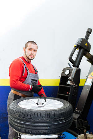 pneumatic tyres: Portrait of mechanic removes car tire and filling air in car tire. Machine for removing rubber from the wheel disc