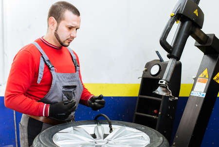 pneumatic tyres: Mechanic filling air in the tire and removes car tire. Machine for removing rubber from the wheel disc Stock Photo