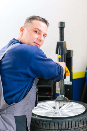 Portrait of mechanician removes car tire. Machine for removing rubber from the wheel disc Stock Photo