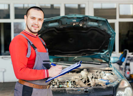 Portrait of a mechanic writing on a clipboard in front of his car