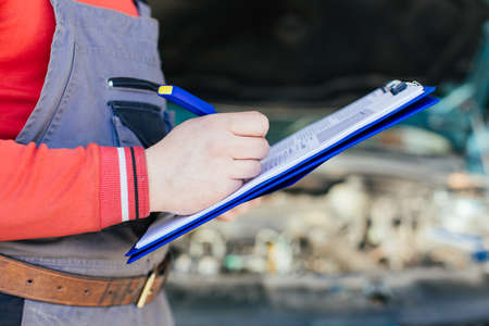 Closeup of mechanic writing on a clipboard in front of his car Stock Photo
