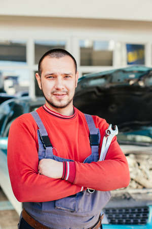 Portrait of a mechanic standing in front of car in auto service garage