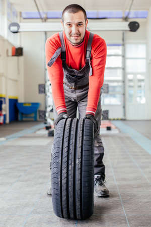 Man pushing a black tire in auto service Stock Photo