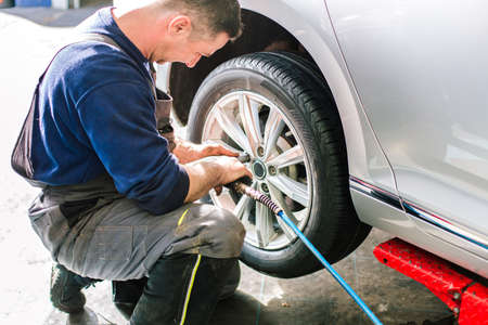 pneumatic tyres: Mechanician changing wheel on car with pneumatic wrench in the auto service garage