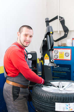 Portrait of mechanic removes car tire and filling air in car tire. Machine for removing rubber from the wheel disc