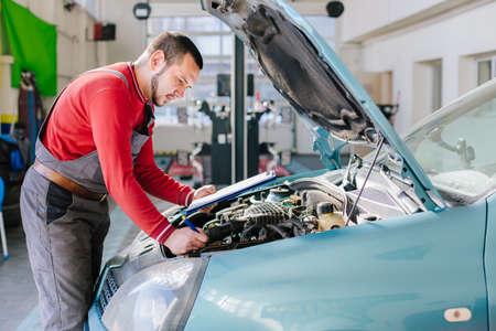 Car mechanic preparing checklist in workshop