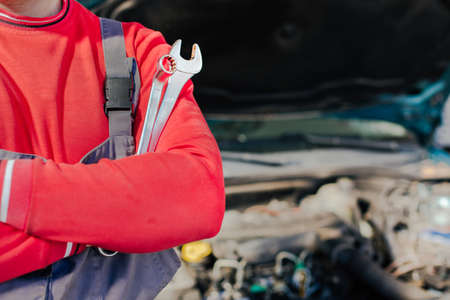 Closeup of hand of professional auto mechanic with wrench, car repair service