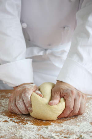 baker making bread , kneading a dough photo