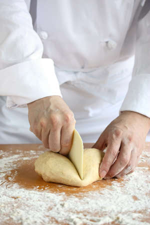 boulangerie: baker making bread,man hands,cutting a dough Stock Photo